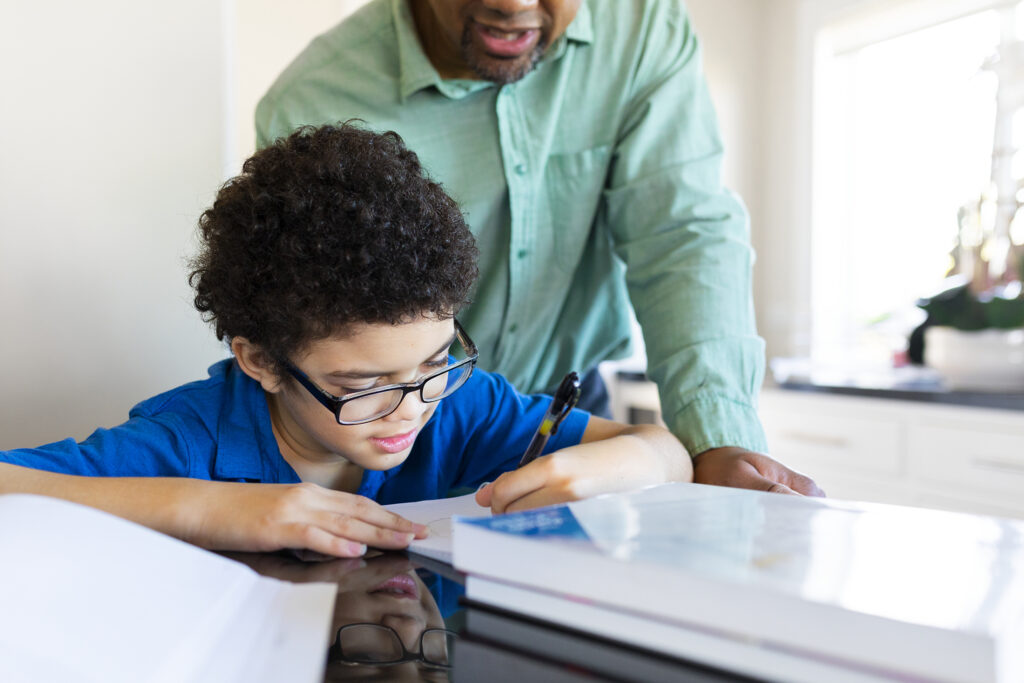 Boy getting homeschooled by his father in the new normal